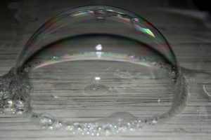 Semi-spherical transparent soap bubble on a grey wood surface.