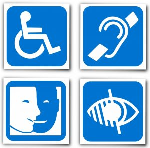 Four universal signs for disabilities: wheelchair access, hearing access, captioning, visual accession. Signs are white on blue background.