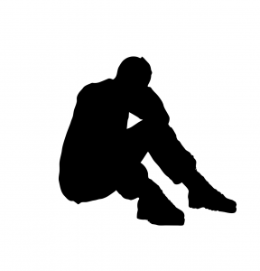 Silhouette of a man seated with elbows on his knees suggesting despair.