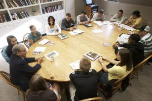 13 students and a professor in discussion around a seminar table.