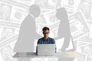 Young man at laptop. Gray-scale background shows a silhouetted man and woman shaking hands, all on a field of dollar bills.