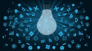 Large light bulb surrounded by small-scale symbols of pursuits in the arts and sciences. Light blue images on dark blue background.