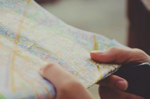 Hands holding a folded paper road map.