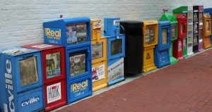 Row of brightly colored newspaper boxes.