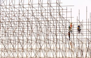 Construction workers climbing a scaffold.